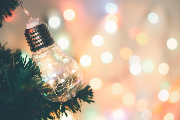 Christmas decoration. light bulb hanging on pine branches christmas tree garland and ornaments over abstract bokeh background with copy space