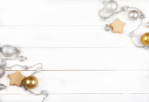 Christmas decoration made of silver balls, beads, cones and cookies on a white wooden surface