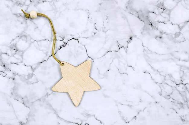 Christmas decoration on a marble background. wooden star, minimalism, flat lay, eco style.