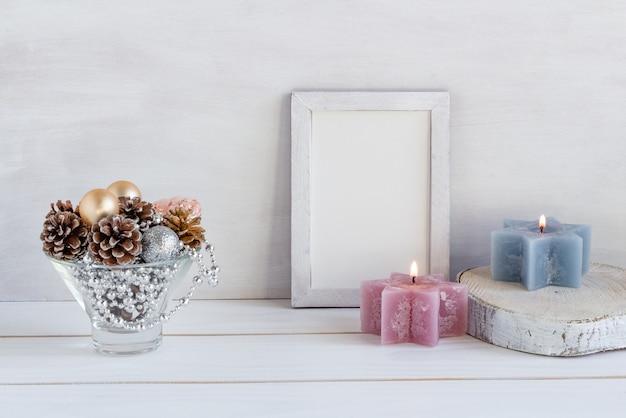 Макет новогоднего украшения в белой рамке с композицией из шишек-бусин, свечей, копией пространства