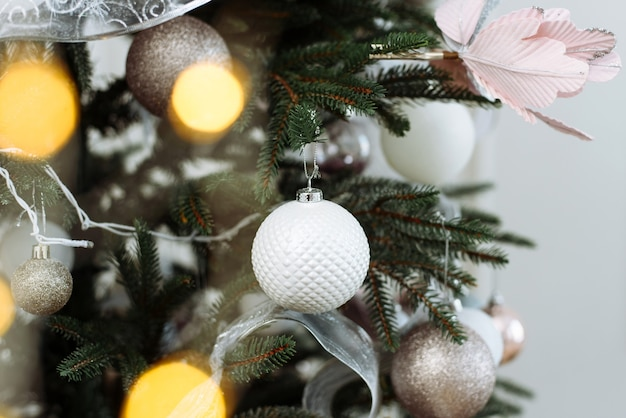 Christmas decoration. new year. gentle pastel colors. pink, silver and white balls on christmas tree branch with garland lights. holiday card.