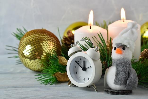 양초, 가문비 나무 가지, 알람 시계 및 펭귄의 크리스마스 장식
