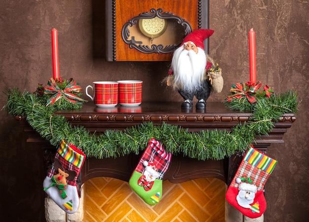 Новогоднее украшение каминных свечей, гирлянд и носков.