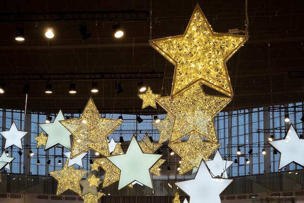 ショッピングセンターの天井のクリスマスデコレーション。電球からの明るい黄色の星