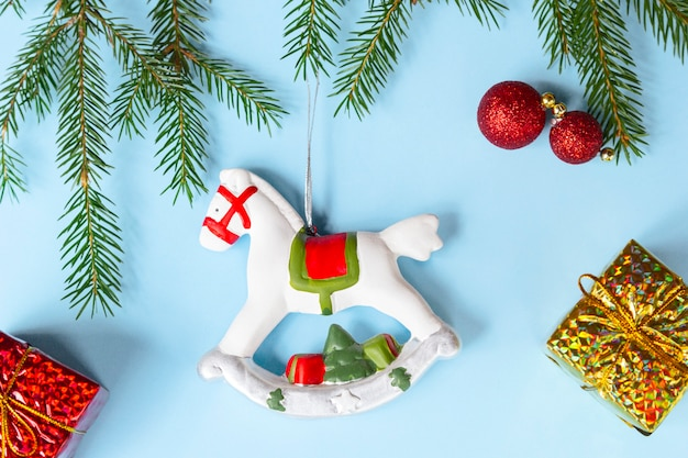 Christmas decoration - old rocking horse, fir branches, golden gifts, balls on light background.