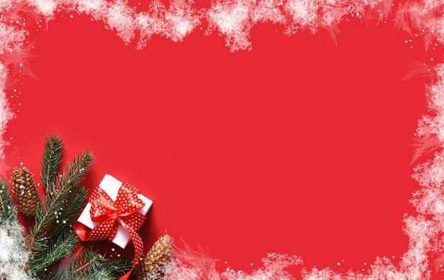 赤い背景、霜と雪の上のクリスマスの装飾。モミとリボンのギフトと赤い背景。