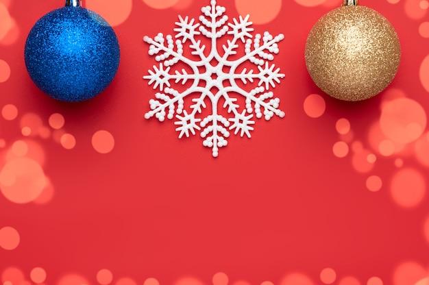 Новогоднее украшение на красном фоне, представляющее два новогодних шара и большую снежинку в центре