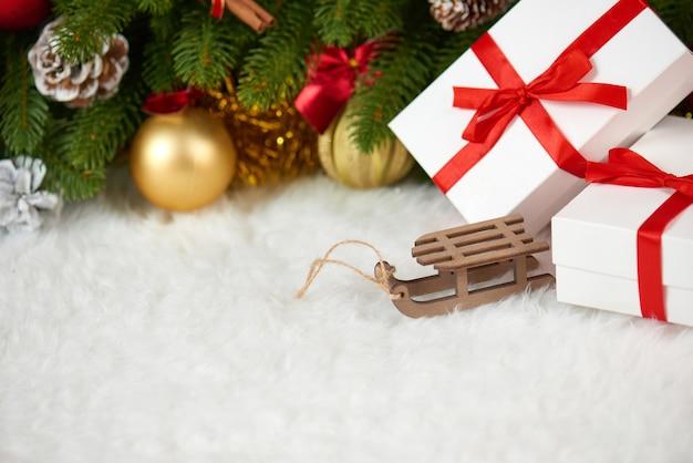 Новогоднее украшение на еловой ветке деревянные сани игрушки подарки