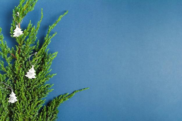 파란색 배경에 전나무 나무의 녹색 지점에 크리스마스 장식