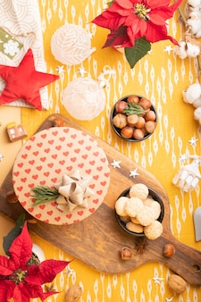 Новогоднее украшение на столе. flatlay с крафтовой подарочной коробкой, пуансеттия, орехи, рождественские украшения