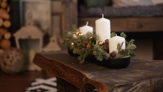 Новогоднее украшение на деревянном столе. рождественские белые свечи на деревянном столе