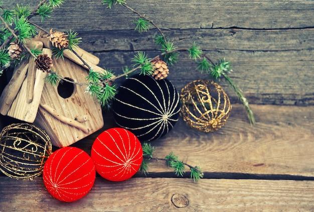 素朴な木製の背景の上のクリスマスの装飾。赤と黒のチャイナスタイルのボールとつまらないもの。レトロなスタイルのトーンの写真