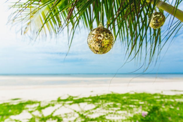Christmas decoration on the palm on the beach on sunny day