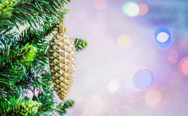 ボケ味の焦点がぼけた色の背景に木の枝にクリスマスの装飾松ぼっくり