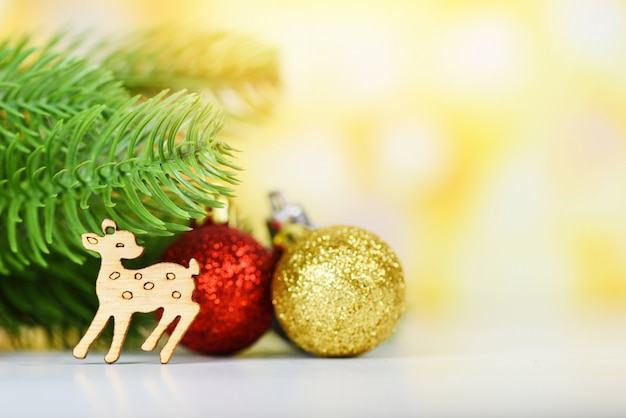 Christmas decoration pine tree with golden red balls and wooden reindeer holiday yellow bokeh