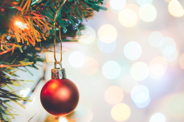 Christmas decoration. red balls hanging on pine branches christmas tree garland and ornaments over abstract bokeh background with copy space