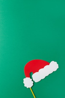 Christmas decoration, red santas hat on stick on green background with copy space