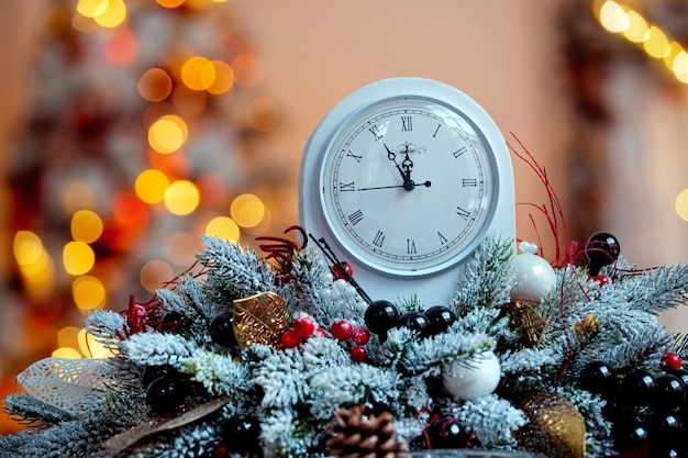 Christmas decoration in room interior. clocks on the table with unfocused backdrop, bokeh effect