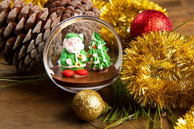 Christmas decoration and santa claus chocolate on wooden table