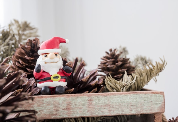 Christmas decoration of santa claus and pine cones in wooden box