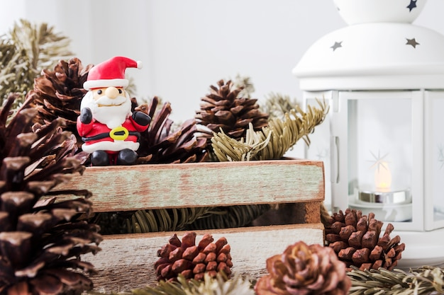 Christmas decoration of santa claus and pine cones on wooden cabinet