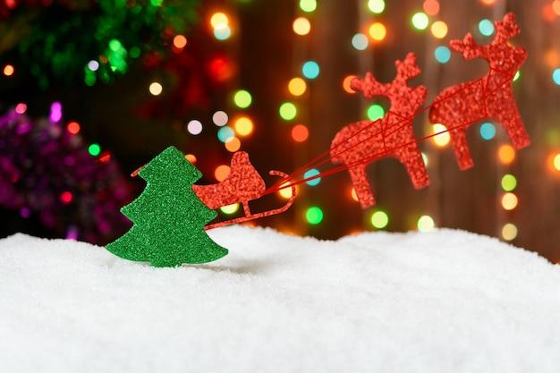 クリスマス装飾そりと背景の花輪の雪の中でトナカイ