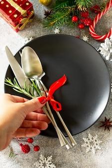 クリスマスデコレーションテーブル女性の手はお祝いのテーブルブラックプレートプレゼントを提供しています