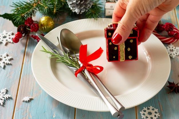 クリスマスの装飾テーブル女性の手はお祝いのテーブルの白いプレートのプレゼントとカトラリーを提供しています