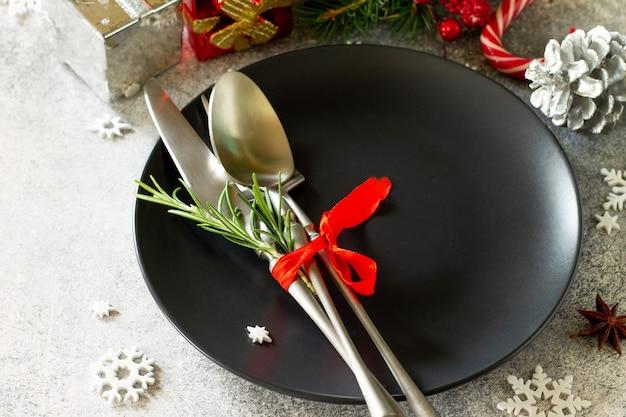 クリスマスの装飾テーブルクリスマスの装飾が施されたお祝いの黒いプレートとカトラリー
