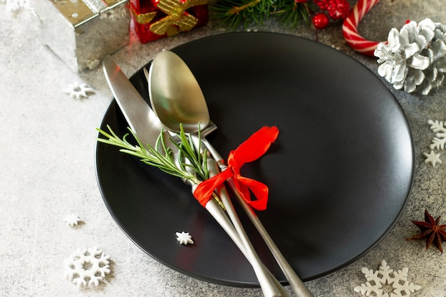 Christmas decoration table festive black plate and cutlery with christmas decor