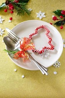 Новогоднее украшение стола праздничная тарелка и столовые приборы с декором на праздничном столе