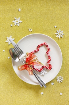 Christmas decoration table festive plate and cutlery with decor on festive table top view flat lay