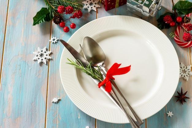 クリスマスの装飾テーブルクリスマスの装飾が施されたお祝いの白いプレートとカトラリー