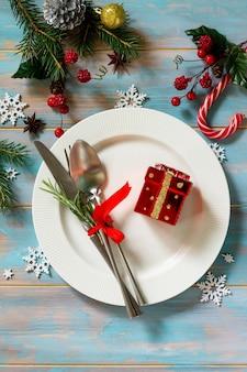 クリスマスデコレーションテーブルクリスマスデコレーション付きのお祝いの白いプレートプレゼントとカトラリー