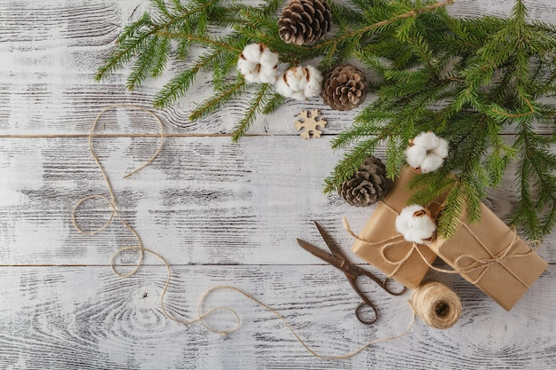 Christmas decoration table: pine and holly branches, handmade gifts with labels, the deer clamp and the set of ornaments on light wood table. top view.