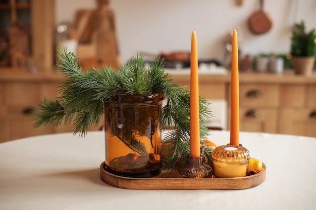 ろうそくが付いているクリスマスの装飾テーブルモミの枝が付いているvasa木製の皿の上の陶磁器のろうそく