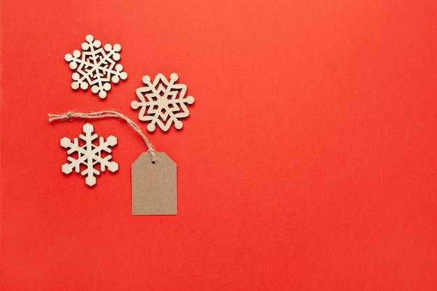 Новогоднее украшение, три маленькие деревянные снежинки и бирка на ярко-красном