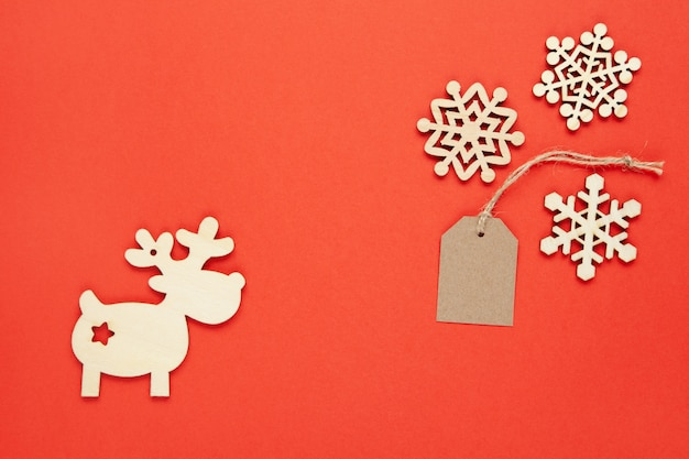 Christmas decoration, three little wooden snowflakes, craft tag, deer on bright red background.