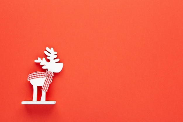 Новогоднее украшение, игрушка белый олень в клетчатом шарфе на красном фоне с копией пространства
