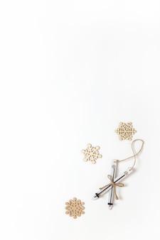 크리스마스 장식, 장난감 나무 스키 및 흰색 배경, 복사 공간에 몇 가지 작은 눈송이. 축제, 새해 개념. 수직, 평평하다. 최소한의 스타일. 평면도