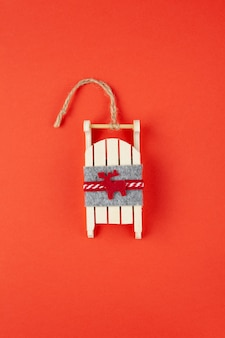 Christmas decoration, tree toy, wooden sled with deer on red background, for social media. festive, new year