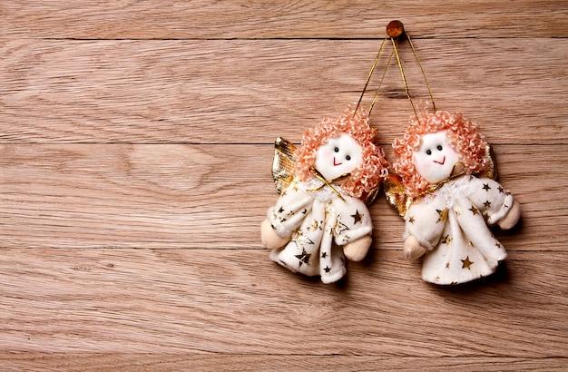 Новогоднее украшение - два ангела, висящие на деревянном фоне