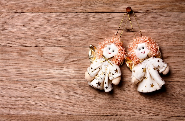 Christmas decoration -  two angels   hanging over wooden background