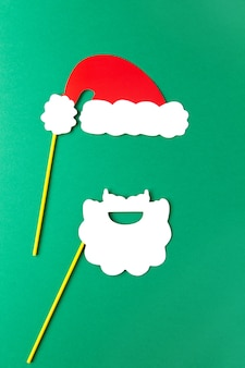Christmas decoration, white beard and red santas hat on sticks on green background
