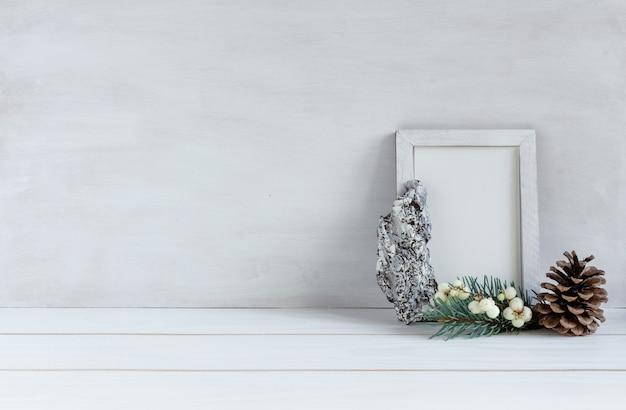 Новогоднее украшение белая рамка, макет с елью и шишкой на белом столе