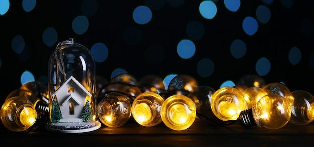 Christmas decoration white house inside glass between lights bulb, blue bokeh dark background