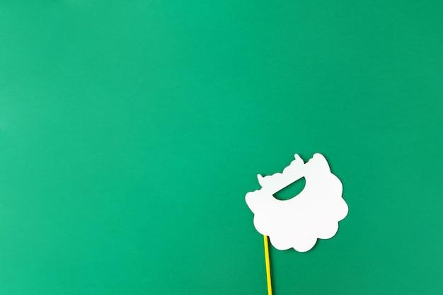 Новогоднее украшение, белая борода санты на палочке на зеленом фоне с копией пространства