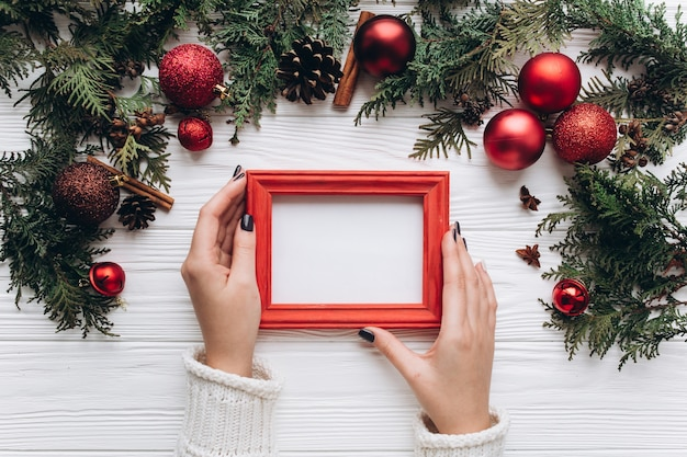 Christmas decoration on the white wooden background. woman holding a photo frame.
