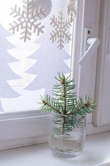 Подоконник новогоднее украшение. ветвь ели в стекле.