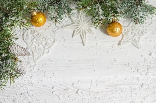 木製のテーブルにボールとモミの木の枝でクリスマスの装飾。フラットレイ